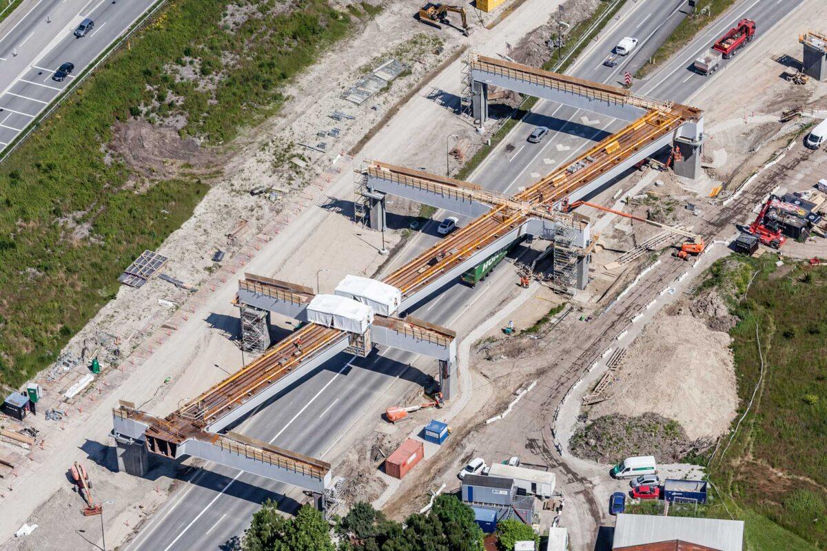 Luftfoto af anlægsarbejder med ny jernbanebro over motorvej
