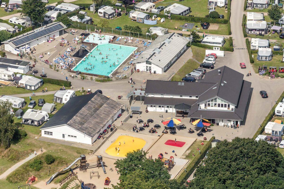 Faciliteter på en campingplads med swimmingpool og servicebygninger set fra luften