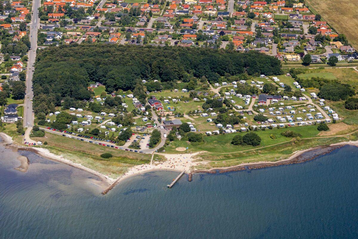 Luftfoto af en campingplads med skov og strand